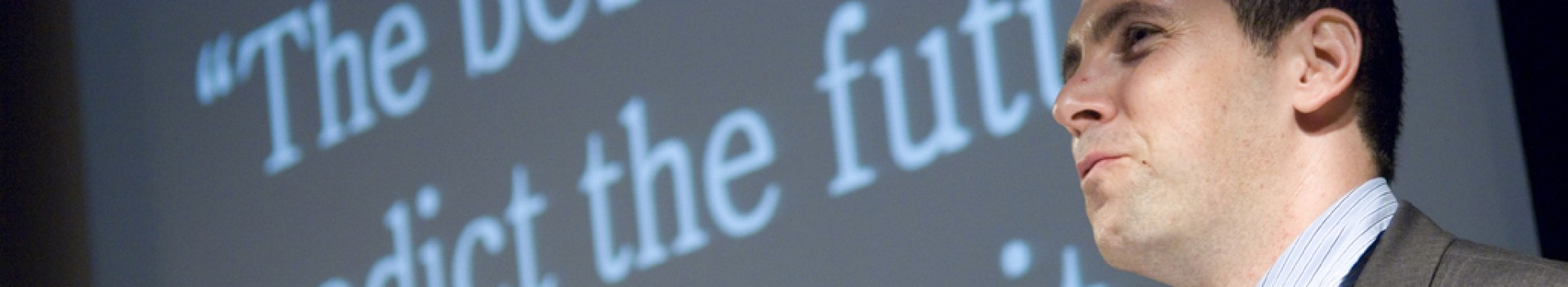 "Man by projector screen showing ""The best way to predict the future is to create it"""