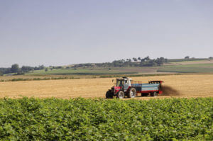 A farmer with his tractor fertilize a field